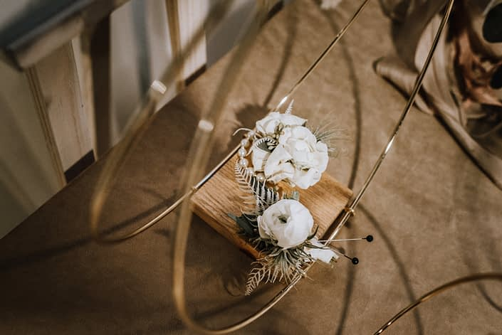An ivory corsage and boutonniere with grey toned greenery accents.