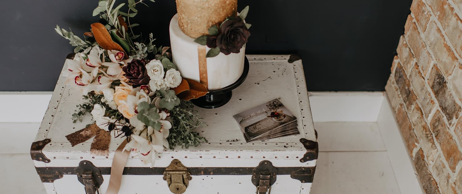 Neutrals Styled Shoot with Down the Aisle - Cake and neutral coloured bouquet with orchids, roses, magnolia leaves and eucalyptus greenery on top of a vintage trunk.