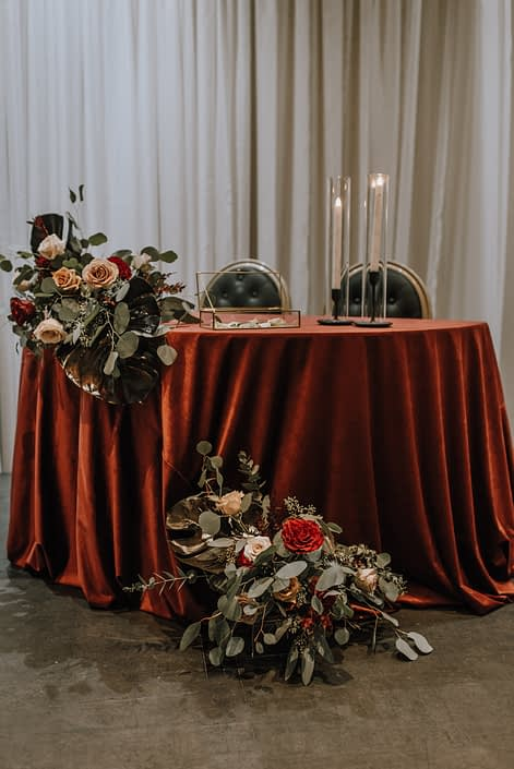 Cambridge Bridal Show 2020 - small couple table covered with red tablecloth decorated with arrangements made of dyed monstera leaves, red and blush roses and eucalyptus greenery.