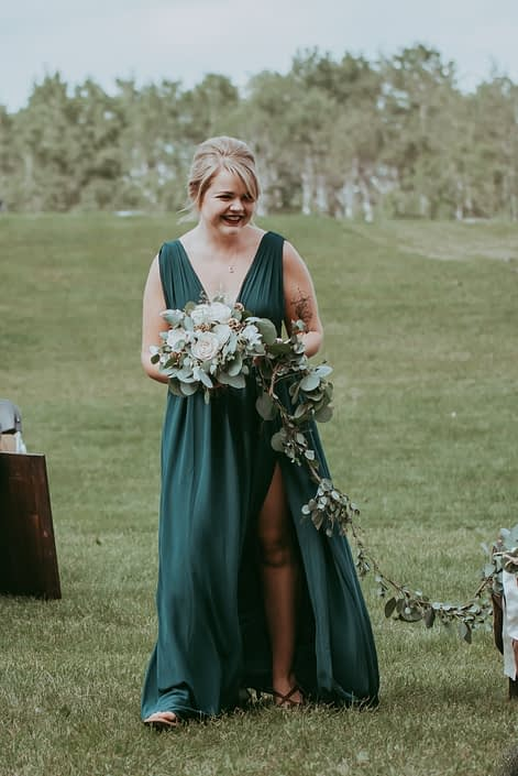 Bridesmaid wearing green floor-length gown while holding natural white and green bouquet and walking dog with eucalyptus garland leash