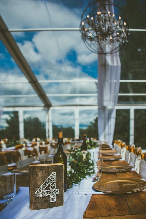 Pine and Pond long tables with gold accents and long greenery garlands.