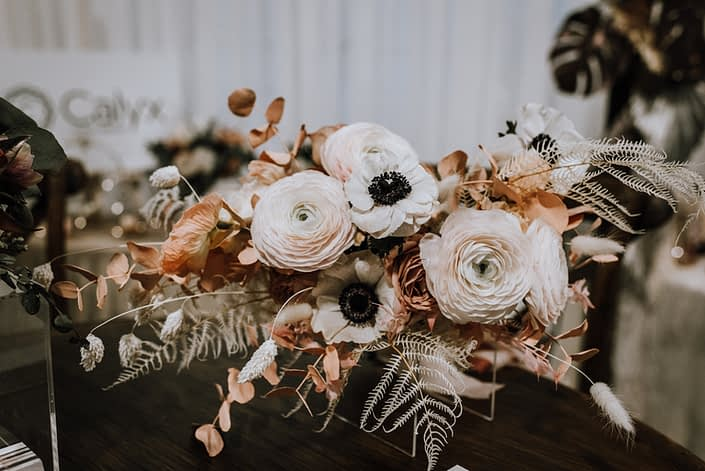 An arrangement made of blush ranunculus, panda anemone and other white and pink botanicals including bunny tails, dried foliage and pink dyed eucalyptus.