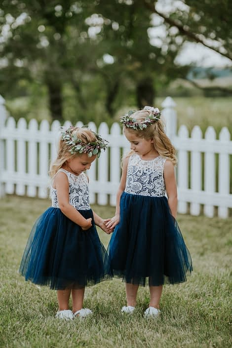 Flower girls wearing white lace and navy tulle dresses and flower crowns made of eucalyptus and pink astilbe.