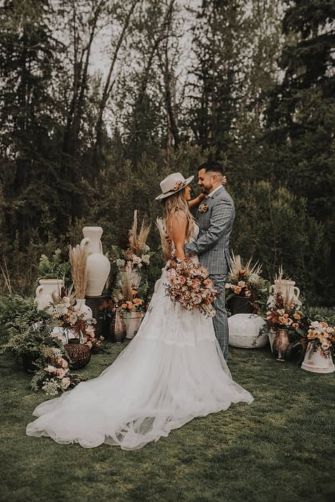 Modern Boho Bride and Groom amongst boho flowers, greenery and decor with terracotta toned bridal bouquet