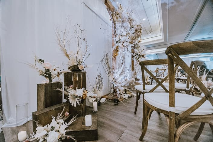 Floral arrangements at the 2020 Down the Aisle Wedding Show designed with dried foraged grasses and branches, pink ranunculus, playa Blanca roses, eucalyptus, and pampas grass on wooden crates.