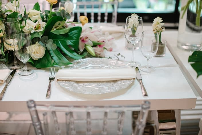 White acrylic table with clear chiavari chairs and white place setting with white floral arrangement and monstera leaves
