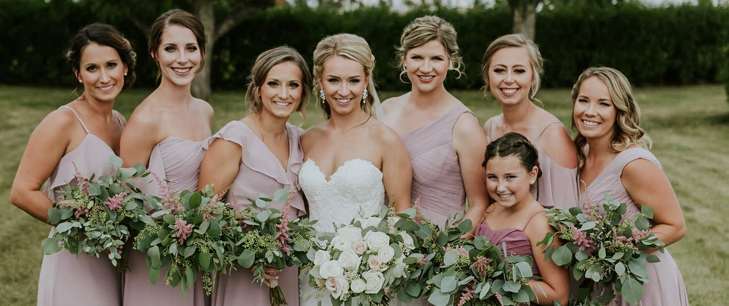 Bride, Brooke, wearing a white lacey dress and holding a blush and ivory bridal bouquet made of white o'hara garden roses, quicksand roses, playa blanca roses, ranunculus, astilbe, wax flower and eucalyptus. Standing with her bridesmaids and jr. bridesmaid wearing blush gowns and holding eucalyptus bouquets with a touch of pink astilbe.