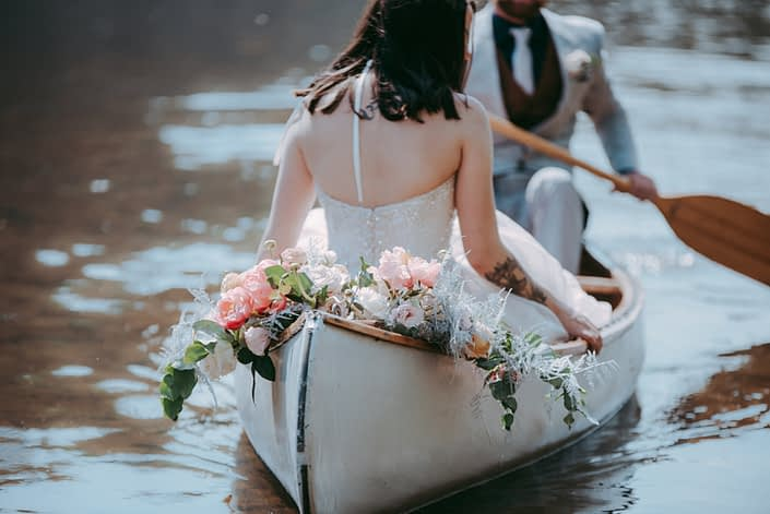Canoe adorned with blush and coral bouquet featuring quicksand and playa blanca roses, coral charm peonies, peach ranunculus, pale pink astilbe, silver plumosa and a mixed variety of eucalyptus greenery.