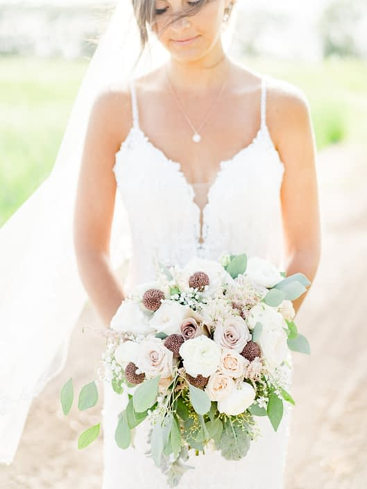 Bride wearing white lace dress and holding a dusty rose bridal bouquet featuring rose gold painted scabiosa pods, white o'hara garden roses, quicksand roses, amnesia roses, astilbe, babies breath, ranunculus, dusty miller and eucalyptus grey toned greenery.