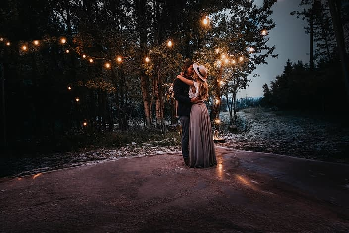 Couple dancing in the woods under twinkly lights