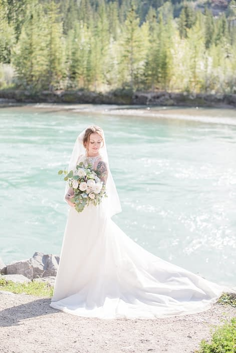 Amy standing on a river bank near Canmore in the Rocky Mountains while holding a pink and blue bridal bouquet featuring white o'hara garden roses, quicksand roses, ranunculus, delphinium, eryngium, astilbe, peach chrysanthemums, and eucalyptus.