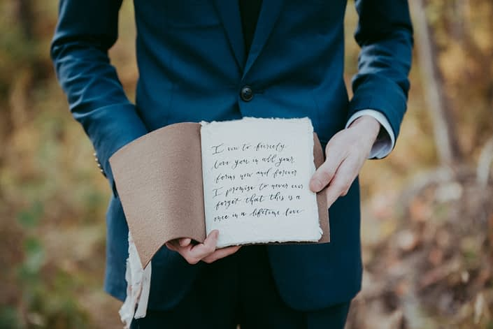 Groom in navy suit holding modern calligraphy leather bound vow book