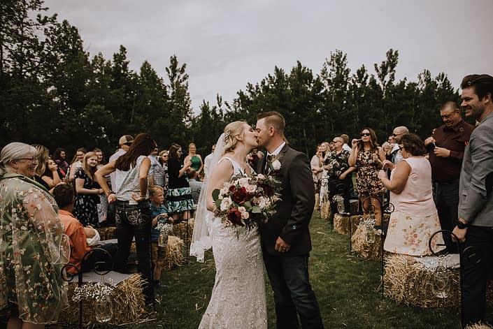 Bride and groom kissing at the ceremony; bride holding rustic red and blush bouquet featuring red charm peonies, blush quicksand roses and eucalyptus greenery.