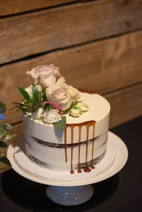 Naked cake with fresh florals on top including quicksand roses, astilbe and eucalyptus greenery.