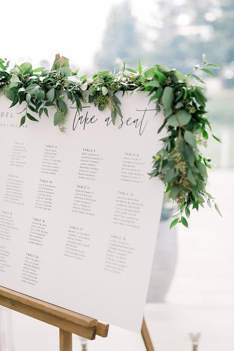 Fresh greenery garland on the seating chart for Kayla and Joel's Timeless White Wedding.
