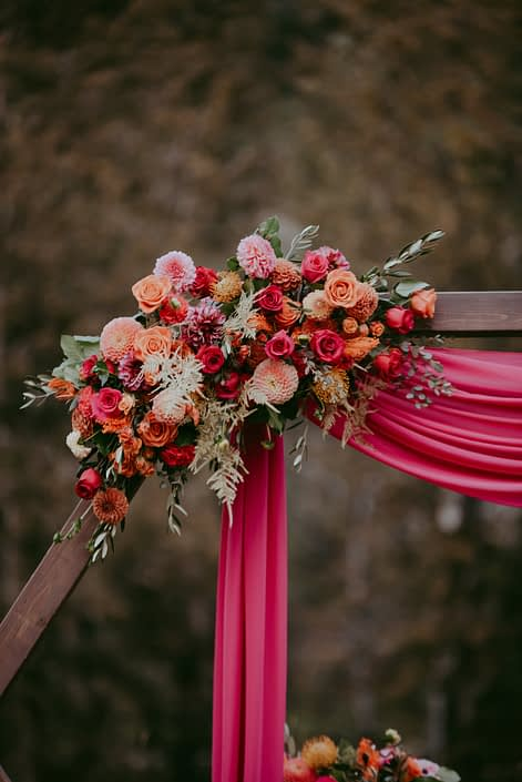 Bold fuchsia and orange wooden archway corner flower arrangement designed with roses, dahlias, zinnias, bleached bracken fern, gold plumosa and olive branches