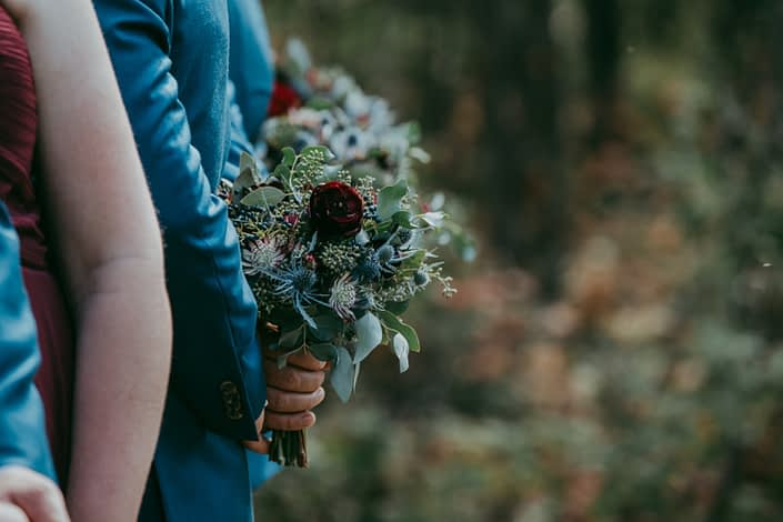 Groomsmen holding burgundy and royal blue bouquet behind back