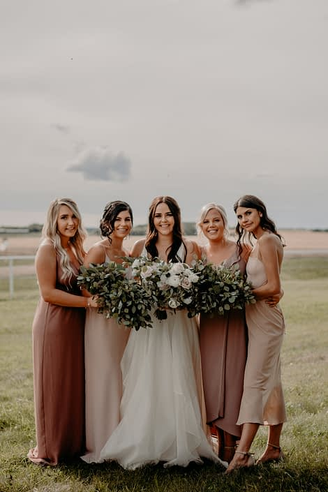 Erika and Colts blush and mauve country wedding - bride wearing white dress and carrying a blush, ivory and white bouquet featuring panda anemones, quicksand roses, ranunculus and lisianthus. The bridesmaids are wearing mauve dresses and carrying fresh mixed eucalyptus bouquets.