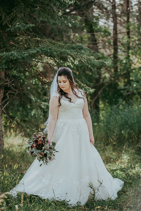 bride with rustic burgundy and dusty rose bouquet in a forest