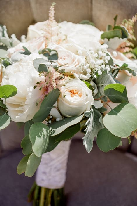 Close-up of Kuera's cream and blush vintage chic bridal bouquet featuring white o'hara garden roses, white peonies, quicksand roses, pale pink astilbe, babies breath, dusty miller and eucalyptus greenery.
