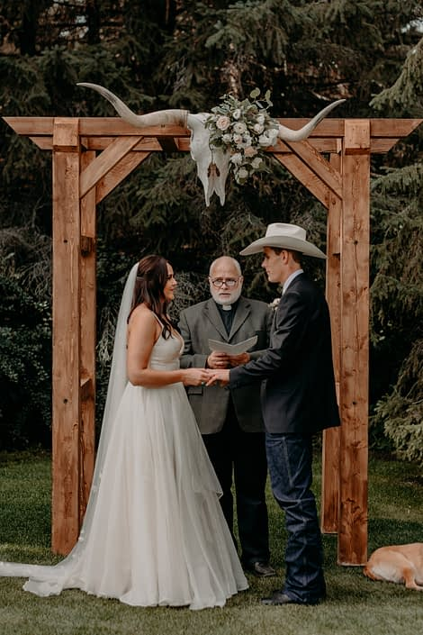 Erika and Colt at their wedding ceremony standing under the wooden archway with longhorn skull at the centre that is decorated with quicksand roses, white lisianthus, panda anemones, ranunculus and eucalyptus greenery.