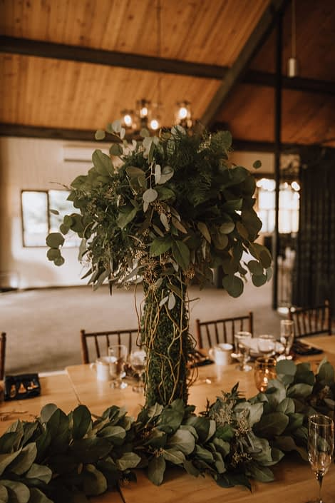 Tall centerpiece with moss covered trunk and mixed eucalyptus topper accented with curly willow and a greenery garland runner on a live edge table with wood chairs in canyon ski resort in Red Deer Alberta