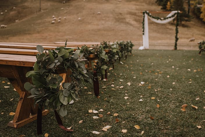 Ceremony decor at Canyon skir resort with eucalyptus hoop aisle markers and mixed greenery garland draped on the archway