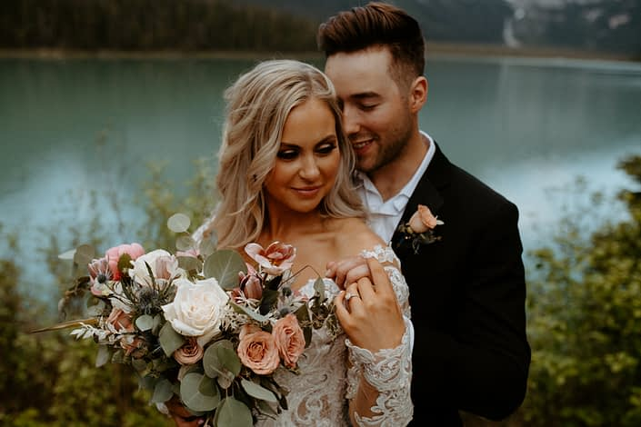 Bride and groom with bridal bouquet designed with toffee roses, playa blanca roses, tulips, eryngium and peonies with bleached Italian Ruscus and eucalyptus greenery
