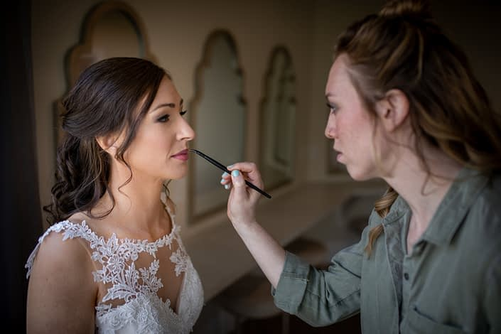 bride in white lace wedding dress with makeup artist