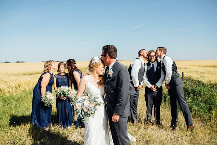 Bridal party being goofy by a field of wheat holding bouquets designed with roses, succulents, blue delphiniums, babies breath and eucalyptus.