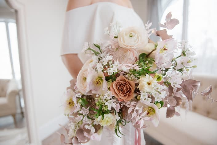 pink, white and rose gold flowers; roses, ranunculus, hellebores, cosmos, alyssum, pink bleached Italian ruscus, rose gold painted plumosa, rose gold painted eucalyptus