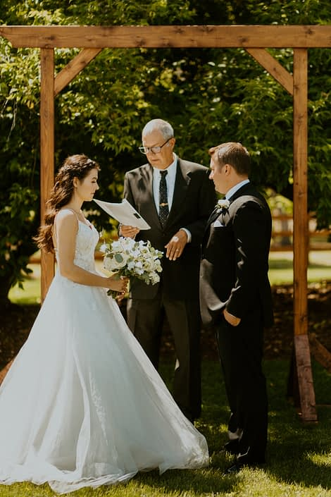 Bride and groom during ceremony with white bridal bouquet and boutonniere.