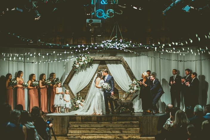 Meagan and Dwayne kiss under a wooden hexagon archway decorated with white, mauve and blush flowers with greenery at their wedding ceremony and are congratulated by their excited dog.