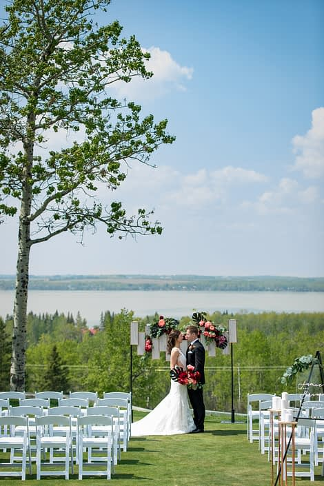 wedding ceremony set up at hilltop wedding venue in sylvan lake with archway backdrop of coral and burgundy and black with bride and groom and bridal bouquet