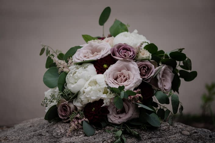 Burgundy and mauve bridal bouquet designed with amnesia and quicksand roses, ranunculus, peonies, dahlias and astilbe with eucalyptus greenery
