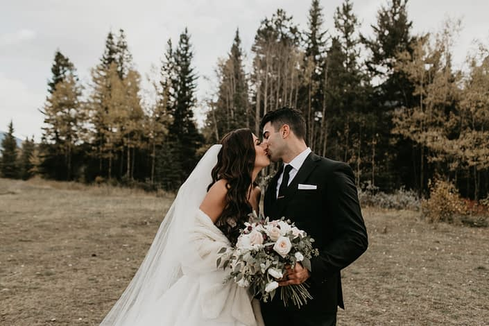 Brittany and Briggs kissing with blush and ivory bouquet designed with white o'hara garden roses, quicksand roses, ranunculus, lisianthus, burgundy astrantia and eucalyptus greenery.