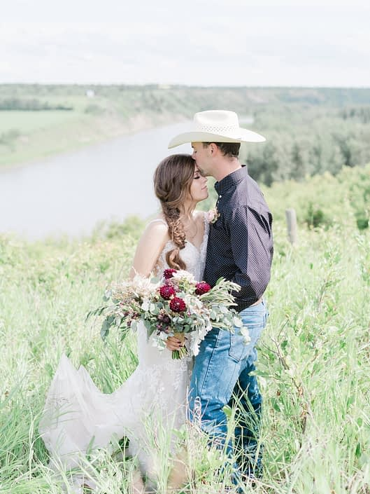 Cowboy groom forehead kissing bride; holding burgundy country chic bridal bouquet featuring burgundy dahlias, quicksand roses, olive branches, dusty miller and eucalyptus.