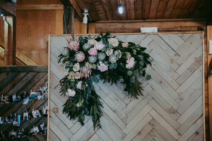 Rustic barnwood backdrop with fresh flower arrangement of king protea, eucalyptus, succulents, peonies and roses