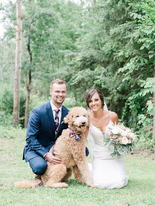 Bride and groom with dog wearing a bow tie. Bride is holding a elegant rustic dusty rose bridal bouquet featuring white o'hara garden roses, rose gold painted scabiosa pods, amnesia and quicksand roses, ranunculus, astilbe, babies breath, dusty miller and eucalyptus.