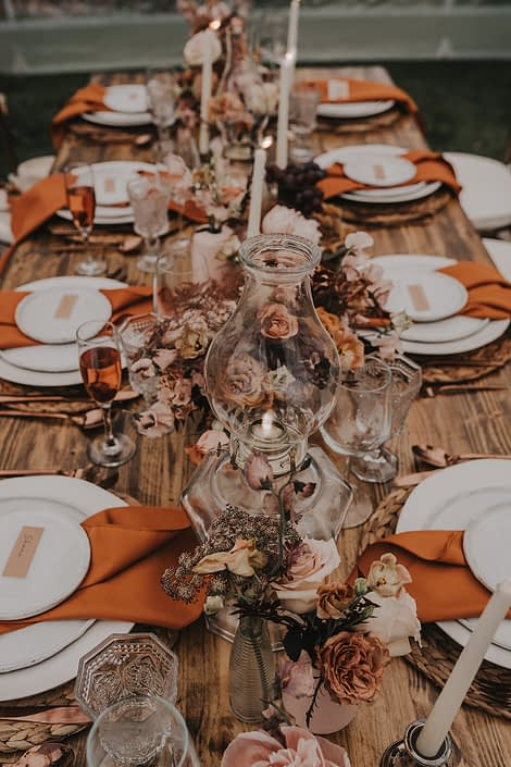Modern boho tablescape centrepiece decorated with flowers, vintage lamps, terracotta napkins and ceramics/pottery