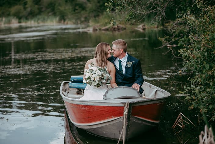 Kylie and Adam in a boat with white bridal bouquet and boutonniere.