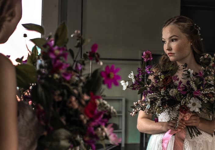 Pink Vintage Photoshoot - model wearing ivory bridal gown holding white, pink and purple wildflower bouquet made of cosmos and greenery tied with trailing ribbons.