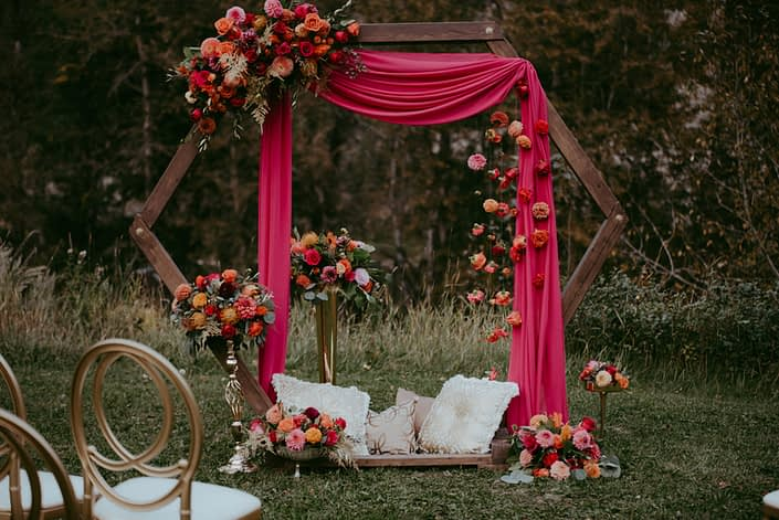 Wooden archway decorated with fuchsia drapery, and colourful fuchsia and orange flower arrangements with gold accents