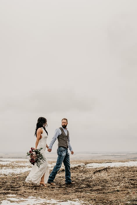 Rustic Boho Chic Wedding - Bride and groom walking together in a snow covered field. Groom wearing vest and jeans. Bride wearing ivory lace dress holding bridal bouquet made of king protea, red peonies, pink roses, plum scabiosa, panda anenome, and eucalyptus greenery.