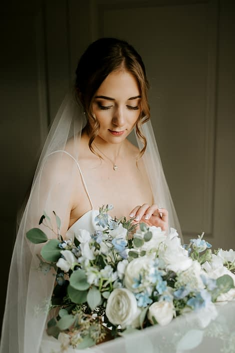 Bride, Erin, with white and blue bridal bouquet designed with delphinium, eryngium, forget me not, white cloud garden rose, ranunculus, sweet pea and eucalyptus greenery