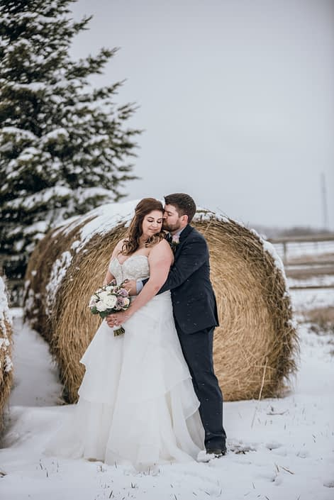 Mauve and Navy Winter wedding bride and groom with bouquet designed with roses, ranunculus, eryngium and eucalyptus