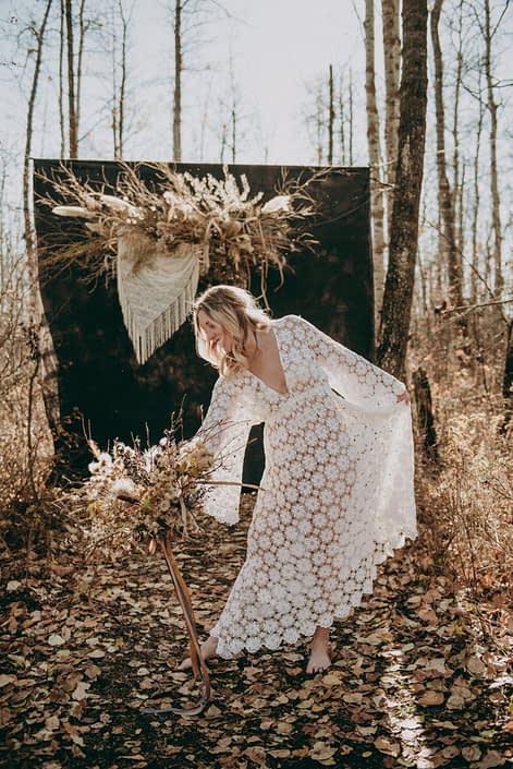 sunlit boho bride barefoot in the woods with a crochet dress and dried floral backdrop