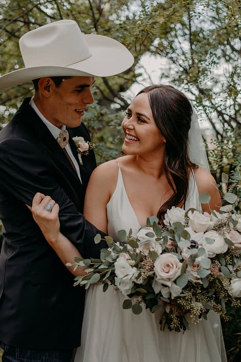 Bride and groom smiling at one another; bride is holding a blush and ivory bridal bouquet featuring panda anemones, lisianthus, quicksand roses and ranunculus with fresh eucalyptus greenery.