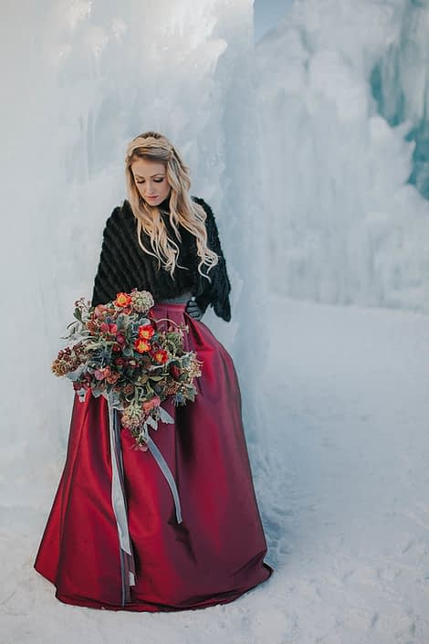 A styled engagement shoot at the edomton ice castles with a black fur shawl, and a bouquet made with red tulips, burgundy frittilaria and burgundy ranunculus