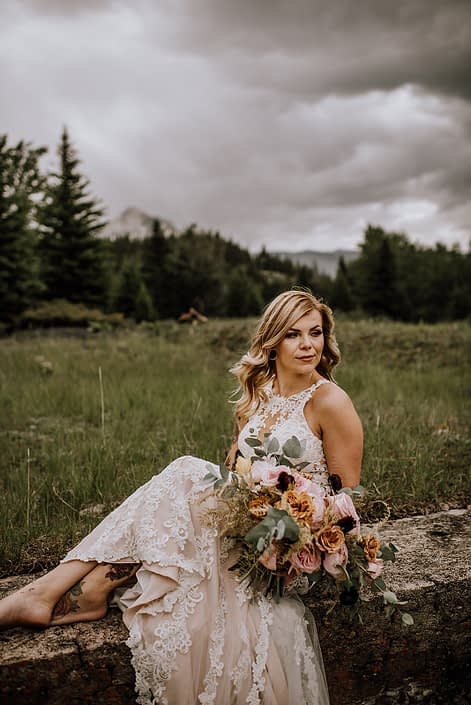 Bride in banff mountains with organic bridal bouquet of toffee roses, pink ohara garden roses, gold plumos and plum ranunculus and cinerea eucalyptus